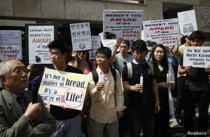 FILE - Ji Seong-ho, center, a North Korean defector living in South Korea and president of Now Action & Unity for Human Rights, attends a rally against Laos' recent repatriation of nine North Korean defectors, in front of the Laotian Embassy in Seoul...