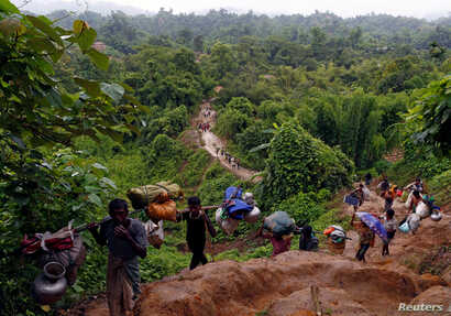 Rohingya refugees climb up a hill after crossing the Bangladesh-Myanmar border in Cox's Bazar, Bangladesh, Sept, 8, 2017.