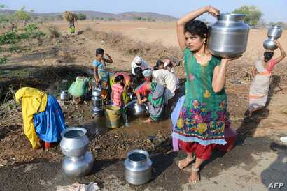 Indian Lambadi tribal villagers fill drinking water from a leaking pipe on a roadside at Chandampet Mandal in Nalgonda east of Hyderabad on April 25, 2016, in the southern Indian state of Telangana.