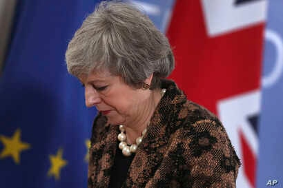 British Prime Minister Theresa May walks by the Union flag and the EU flag as she departs a media conference at an EU summit in Brussels, Dec. 14, 2018.