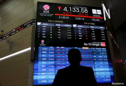 FILE - A trader stands in front of an electronic board at the Indonesia Stock Exchange (IDX) in Jakarta.