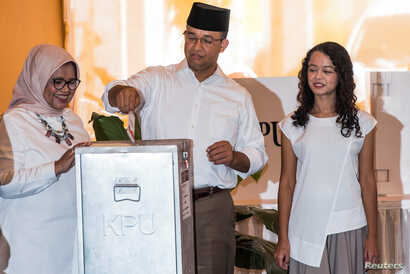 Anies Baswedan (C) is seen with his wife Fery Farhati Ganis (L) and his daughter Mutiara Annisa Baswedan as he casts his ballot during an election for Jakarta's governor in Jakarta,  February 15, 2017 in this photo taken by Antara Foto.