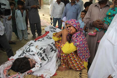 "FILE - In this picture taken on July 18, 2016, the mother of Pakistani slain social media star Qandeel Baloch mourns besides her dead body in Shah Sadderuddin, Pakistan. Baloch was killed by her brother for what he called ""intolerable"" behavior."