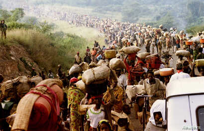 FILE - Rwandese refugees cross Rusumo border to Tanzania from Rwanda carrying their belongings even goats, mattresses and cows, May 30, 1994.