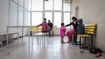 A family wait their turn to make a legal crossing at one of the official camps by the Serbia/Hungary border. Hungary now only allows 10 refugees and migrants to cross a day. (J. Owens for VOA)