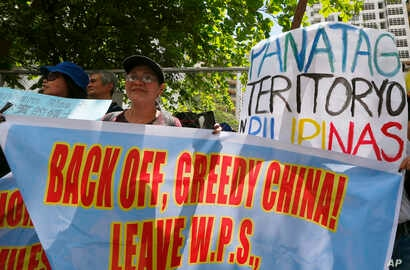 """FILE - Protesters display placards in front of the Chinese Consulate to protest China's alleged continuing """"militarization"""" of the disputed islands off the South China Sea including a plan to build a monitoring station on Scarborough Shoal, March 24,..."""