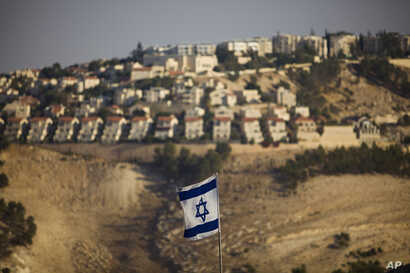 FILE - An Israeli flag is seen near the West Bank Jewish settlement of Maaleh Adumim on the outskirts of Jerusalem in a Sept. 7, 2009, photo.