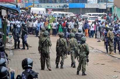 Ugandan army soldiers stand in front of a crowd during protests by supporters of Ugandan pop star-turned-lawmaker Bobi Wine, whose real name is Kyagulanyi Ssentamu, in Kampala, Uganda, Aug. 31, 2018.