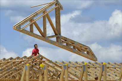 In this July 17, 2014 photo, construction workers build a commercial complex in Springfield, Ill.