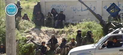 This image posted on the Twitter page of Syria's al-Qaida-linked Nusra Front, April 25, 2015, shows Nusra Front fighters in the town of Jisr al-Shughour, Idlib province, Syria.