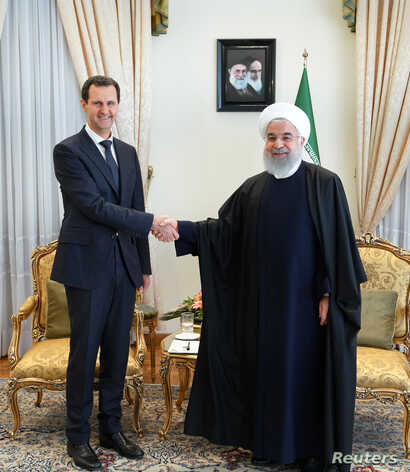 A Syria's President Bashar al-Assad shakes hands with Iranian President Hassan Rouhani in Tehran, in this handout released by SANA, Feb. 25, 2019.
