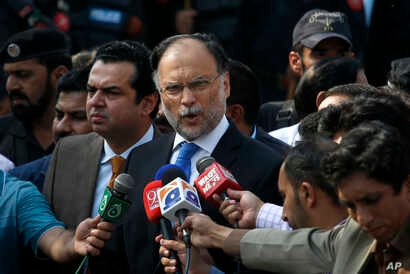 Pakistani Interior Minister Ahsan Iqbal talks to media outside the accountability court where Pakistan's former Prime Minister Nawaz Sharif appeared, in Islamabad, Pakistan, Monday, Oct. 2, 2017. A Pakistani court has postponed the indictment of form...