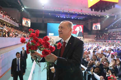 Turkey's President Recep Tayyip Erdogan throws flowers to his supporters as he arrives to deliver a speech at his ruling Justice and Development Party (AKP) congress in Ankara, Aug. 18, 2018.