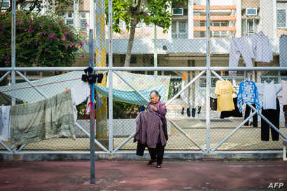 An elderly woman collects items of laundry that were hung out to dry along fences in a playground of a government housing estate in Hong Kong, Dec. 20, 2018.