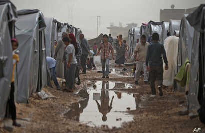 Syrian Kurdish refugees who fled Kobani, go about at a refugee camp in Suruc, on the Turkey-Syria border, Oct. 11, 2014.