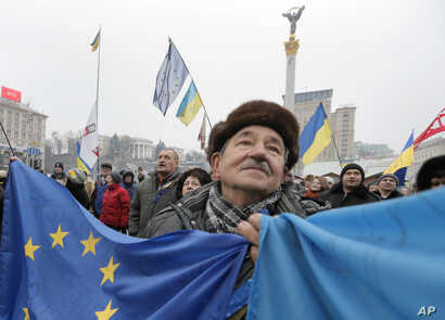 A pro-European Union activist  with Ukrainian and the European Union flags stands with others in Independence Square in Kyiv, Ukraine, Dec. 20, 2013.