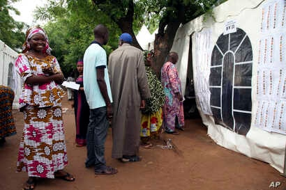 Malians wait to cast their ballot during the Presidential elections in Bamako, July 29, 2018.