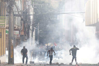 Demonstrators are pictured amid tear gas during a protest as Honduran President Juan Orlando Hernandez is sworn in for a new term in Tegucigalpa, Honduras, Jan. 27, 2018.