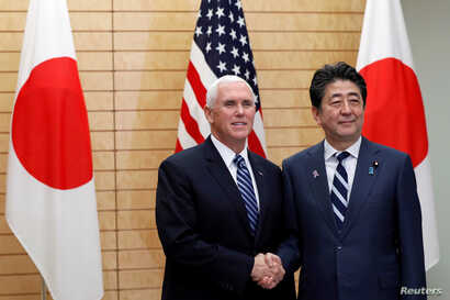 Vice President Mike Pence shakes hands with Japanese Prime Minister Shinzo Abe at Abe's official residence in Tokyo, Nov. 13, 2018.