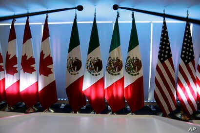 National flags representing Canada, Mexico, and the U.S. are lit by stage lights at the North American Free Trade Agreement, NAFTA, renegotiations, in Mexico City, Sept. 5, 2017.