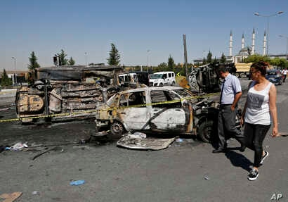 Turkish citizens walk past burnt and destroyed police and civilian vehicles near the presidential palace, in Ankara, Turkey, July 17, 2016, that were attacked by a Turkish airstrike during a military coup late Friday.
