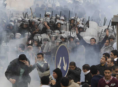 FILE - In this Jan. 28, 2011 file photo, Egyptian anti-government activists clash with riot police in Cairo, Egypt. The simmering frustrations in Egypt _ more than four months after the stunning downfall of Hosni Mubarak _ offer a sobering counterpoi...