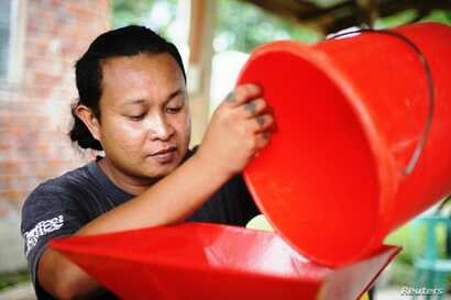 Dayen Cardeno processes coffee beans at a community centre in Mindanao, the Philippines, March 26, 2018.