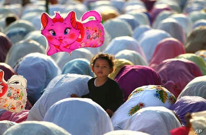 A Muslim girl holds a balloon during a morning prayer marking the Eid al-Adha holiday on a street in Jakarta, Indonesia, Oct. 15, 2013.