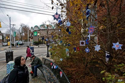Stars of David hang from bushes outside the post office in the Squirrel Hill neighborhood of Pittsburgh, Nov. 20, 2018. They are part of a Facebook group-initiated project, Jewish Hearts for Pittsburgh. A sign thanks people for participating in an ac...