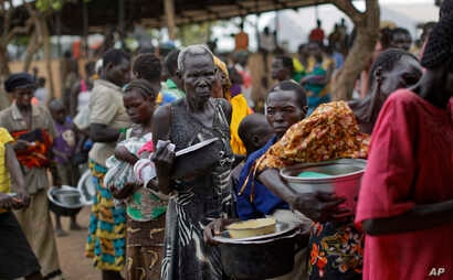 FILE - South Sudanese refugees queue to receive a lunch of maize mash and beans, at the Imvepi intake center, where newly-arrived refugees are processed before being transferred to the nearby Bidi Bidi refugee settlement, in northern Uganda, June 6, ...
