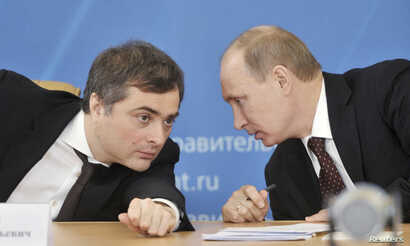 Russian Prime Minister Vladimir Putin, right, talks with Deputy Prime Minister Vladislav Surkov as they attend a meeting in Kurgan, Feb. 13, 2012.