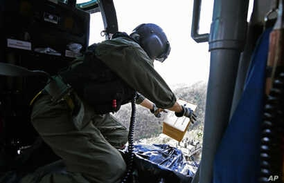 This U.S. Coast Guard image shows Petty Officer 2nd Class Kenneth Krowel dropping a box of MRE's to stranded residents near Utuado, Puerto Rico, Oct. 3, 2017. Nearly two weeks after the storm, 95 percent of electricity customers remain without power....