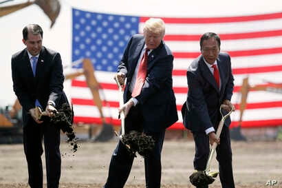 FILE - President Donald Trump, center, along with Wisconsin Gov. Scott Walker, left, and Foxconn Chairman Terry Gou participate in a groundbreaking event for the Foxconn facility in Mt. Pleasant, Wis., June 28, 2018.