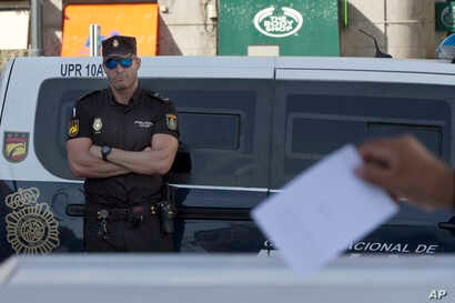 A national police officer watches a person casts a symbolic 'No' vote during protest against the Catalonian referendum in Madrid, Spain, Sept. 29, 2017.