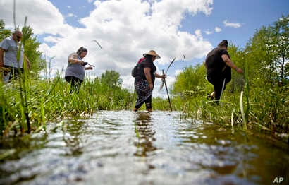 Kimberly Loring, from right, Roxanne White, Lissa Loring and George A. Hall, cross a creek looking for clues during a search for the Loring's sister and cousin, Ashley HeavyRunner Loring, who went missing in 2017 from the Blackfeet Indian Reservation...