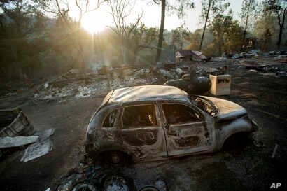 A vehicle scorched by a wildfire rests in a clearing on Wolf Creek Road near Clearlake Oaks, California, June 24, 2018.