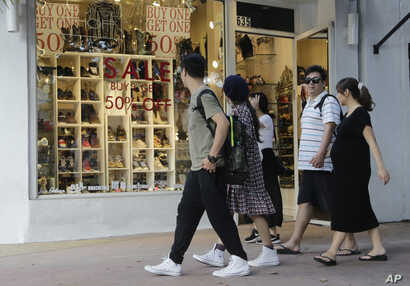FILE - People walk past a shoe store at Lincoln Road Mall in Miami Beach, Fla., Feb. 3, 2016. A University of Michigan survey's measure of current economic conditions, released Jan. 18, 2019,decreased to 110.0 from a reading of 116.1 in December 20...