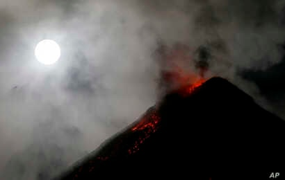 The super blue blood moon sets before dawn as lava cascades down the slopes of Mount Mayon volcano during a mild eruption as seen from Sto. Domingo township, Albay province around 340 kilometers (200 miles) southeast of Manila, Philippines, Feb. 1, 2...