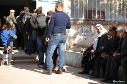 Voters queue to cast their ballots at a polling station in Qamishli, Syria, Dec. 1, 2017.