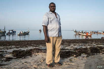 Saff Sall stands ashore for a quick portrait as his crew members load their fishing boat, which is headed to neighboring Guinea Bissau for the next two weeks, May 30, 2017. (R. Shryock/VOA)