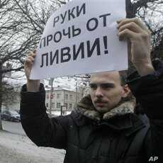 An activist of an anti-Kremlin opposition group, The Left Front, holds a poster reading 'Hands off Libya' during his picket at the NATO representative office in Moscow, Russia, March 19, 2011