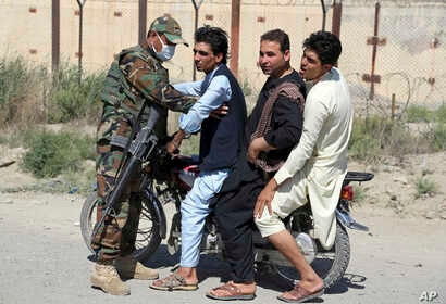 In this July 10, 2018, photo, an Afghan national army soldier searches three men on a motorcycle at a checkpoint on the outskirts of Kabul, Afghanistan.