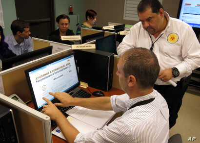 FILE - Puerto Rico Health Department workers monitor social media for Zika related issues at the department's headquarters in San Juan, Puerto Rico.
