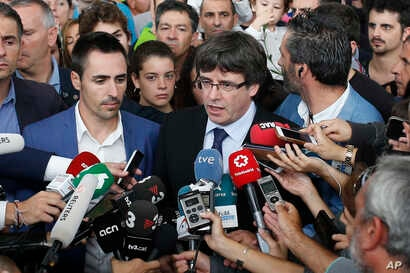 Catalan President Carles Puigdemont, center, speaks to the media at a sports arena designated a polling station by the Catalan government, in Sant Julia de Ramis, near Girona, Spain, Oct. 1, 2017.