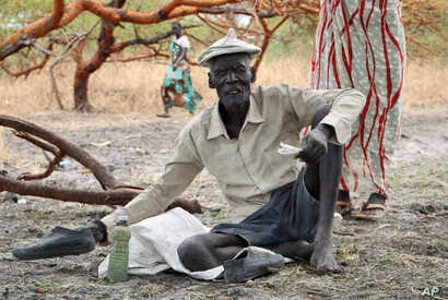 Gatdin Bol, 65, who fled fighting and now survives by eating fruit from the trees, sits under a tree in the town of Kandak, South Sudan. Five years into South Sudan's civil war more than 7 million people are facing severe hunger without food aid, acc