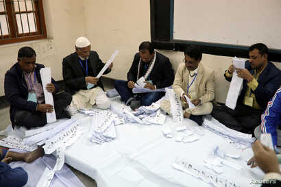Presiding officers count votes at a voting center after the session has ended in Dhaka, Bangladesh, Dec. 30, 2018.