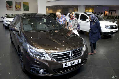 FILE - In this July 16, 2015 photo, Iranians look at a Renault sedan at a dealership in northern Tehran, Iran.