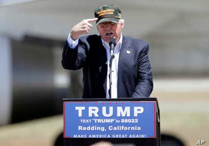 """Republican presidential candidate Donald Trump gestures to a his camouflaged """"Make America Great"""" hat as he discuses his support by the National Rifle Association at a campaign rally at the Redding Municipal Airport, June 3, 2016, in Redding, Califor"""