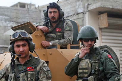 FILE - In this March 24, 2018 file photo, Turkish soldiers atop an armored personnel carrier secure the streets of the northwestern city of Afrin, Syria.
