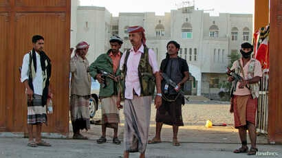 Armed men loyal to Yemen President Abd-Rabbu Mansour Hadi stand guard outside a local authority compound after taking it over in Yemen's southern port city of Aden, Feb. 16, 2015.